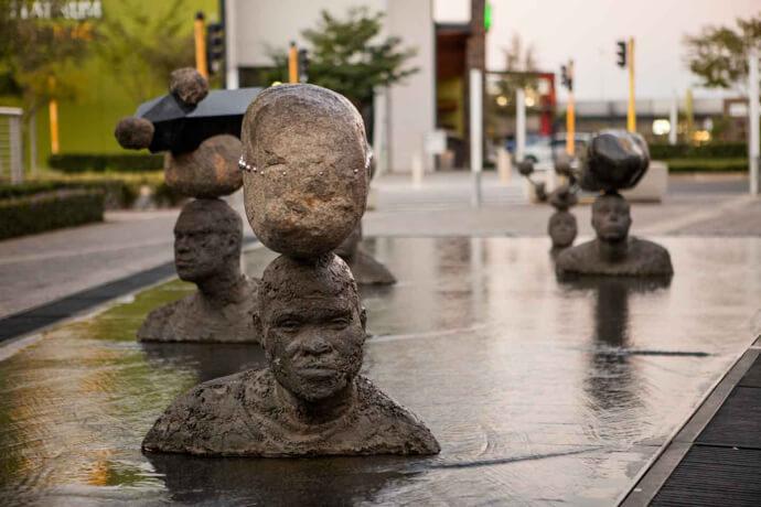 Head and shoulders sculptures of men at Platinum Square in Rustenburg